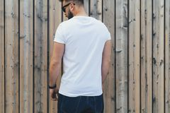 Young bearded hipster man dressed in white t-shirt and sunglasses is stands outdoor against wood wall. Mock up. Royalty Free Stock Photos