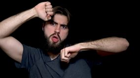 Young bearded hipster man isolated over black background while listening music and dancing. Attractive young man in grey royalty free stock photos