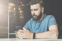 Young bearded hipster man sits at a table in a cafe and uses a smartphone. Guy is chatting, working, blogging, learning Stock Photo
