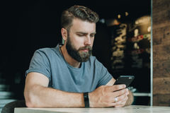 Young bearded hipster man sits at a table in office and uses a smartphone. Guy is chatting, blogging, learning online Royalty Free Stock Photos