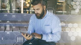 Young bearded hipster man sits and uses digital tablet. In foreground are virtual icons with people, digital gadgets. Young bearded hipster man sits and uses stock image