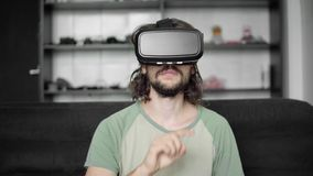 Young bearded hipster man start using his VR headset display for navigation in the vr-program or virtual reality game. While sitting on sofa at home in the