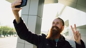 Young bearded hipster man taking selfie picture using smartphone camera outdoors at city street Stock Photo