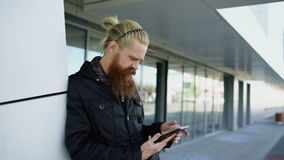 Young bearded hipster man using smartphone fo internet surfing near offfice building stock video