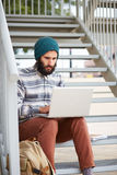 Young bearded hipster student using computer outdoors Stock Images