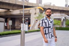Young bearded Indian man against view of the skytrain station outdoors. Portrait of young bearded Indian man exploring in the city outdoors royalty free stock images