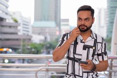Young bearded Indian man thinking and using phone against view of the city streets royalty free stock images