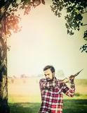 Young bearded Lumberjack with Ax gut a tree on summer nature background. Stock Photography