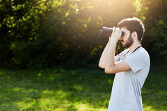 Young bearded male looking through binoculars while standing at green field, observing something. Handsome young guy having expedi Royalty Free Stock Photos