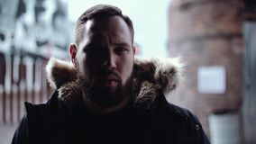 Young bearded male model in winter jacket looks into camera at urban area. Young bearded caucasian male model in winter jacket looks into camera at urban area stock footage