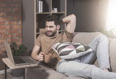 Young bearded male is resting at home stock photos