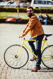 Young bearded man adjusting eyewear and looking at camera while sitting on his bicycle outdoors Royalty Free Stock Photography