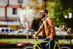 Young bearded man adjusting eyewear and looking at camera while sitting on his bicycle outdoors. Full length of confident young bearded man adjusting eyewear and Royalty Free Stock Image