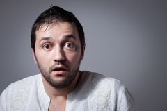Young bearded man with astonished expression. On dark background Royalty Free Stock Photo