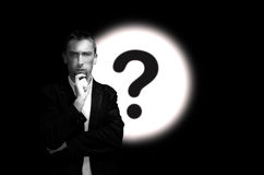 Young bearded man on background with question mark. Idea concept Royalty Free Stock Photos