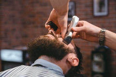 Young bearded man during beard grooming in barber shop. Young bearded men during grooming of beard using trimmer in barber shop royalty free stock images