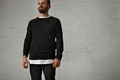 Young bearded man in blank black shirt. Bearded brutal hipster wearing a blank black longsleeve shirt with a white t-shirt underneath and black jeans against Royalty Free Stock Photos
