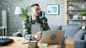 Young man blogger recording audio for broadcasting at home using mic and laptop. Young bearded man blogger is recording audio for global broadcasting at home stock video footage