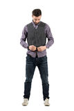 Young bearded man buttoning waistcoat looking down stock photo