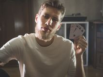 Young bearded man in casual holding playng cards show some tricks at home portrait. Young bearded man in casual holding playng cards to show some tricks at home royalty free stock images