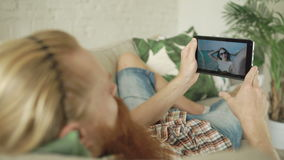 Young bearded man chatting with girlfriend using tablet computer lying in sofa at home. Closeup of Young bearded man chatting with girlfriend using tablet stock footage