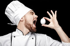 Young bearded man chef In white uniform holds  egg on black background Royalty Free Stock Photos