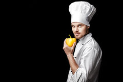 Young bearded man chef In white uniform holds yellow bell pepper on  black background Stock Photo