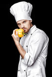 Young bearded man chef In white uniform holds yellow bell pepper on  black background Stock Images