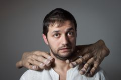 Young bearded man choked by two huge hands. On dark background Stock Images