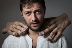 Young bearded man choked by two huge hands. On dark background Stock Photo