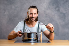 Young bearded man with cooking pot Stock Image