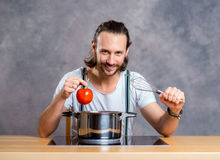 Young bearded man with cooking pot Royalty Free Stock Photos