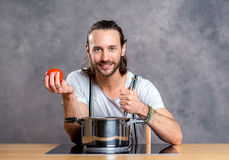 Young bearded man with cooking pot Stock Photo