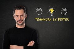 Young bearded man with crossed arms, heads with brains, lightbulb-idea and text `Teamwork is better` on a blackboard background. royalty free stock images