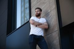Young bearded man crossed her arms over his chest against of office building royalty free stock photos