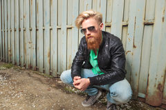 Young bearded man crouching outdoor Royalty Free Stock Photos