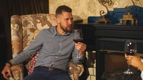 Young bearded man on a date with a glass of wine in his hands talking to his girlfriend. Enamored couple sitting in a chair, hug each other and drinking vine in stock video footage