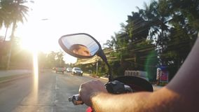 Young bearded man driving motorbike on tropical island during beautiful sunset in slow motion while traveling. Thailand stock footage