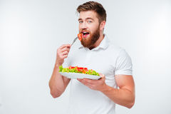 Young bearded man eating salad Royalty Free Stock Photography
