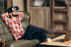 Young bearded man enjoying virtual reality glasses. Relaxed smiling guy in vr headset watching movie at home. Innovation, modern technology, rest, cyberspace stock image