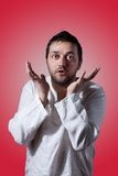 Young bearded man expressing with his hands. On red background Royalty Free Stock Photo