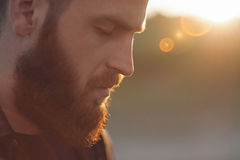 Young bearded man with eyes closed. Young bearded man with closed eyes on the background of the sun's rays Royalty Free Stock Photo