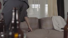Young bearded man gets up from the sofa and walks away, grabbing his cellphone and headphones. Blurred empty beer stock footage