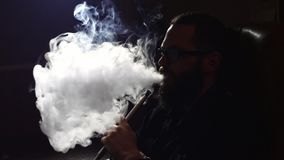 Young bearded man in glasses smokes a hookah and blow out smoke closeup on black background in slow motion in 4k. Young bearded man in glasses smokes a hookah stock video