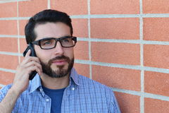 Young bearded man with glasses talking on mobile phone  on red brick wall modern background.  Stock Photography