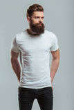 Young bearded man. Handsome young bearded man is looking away while standing against gray background Royalty Free Stock Photo