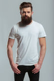 Young bearded man. Handsome young bearded man is looking at camera while standing against gray background Stock Photos