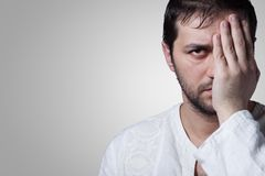 Young bearded man with his hand covering an eye. On grey background Stock Image