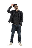Young bearded man holding cap wearing sunglasses looking at camera Royalty Free Stock Photo