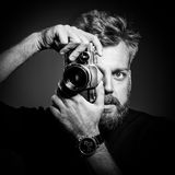 Young bearded man holding retro camera. Against black background. Confident photographer shooting at his studio. Black and white photography royalty free stock image